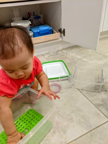toddler playing with container for fine motor